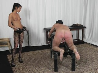 Slave is whipped by a hot topless mistress