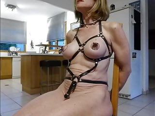 slave equipped with harness and bondage string is pierced